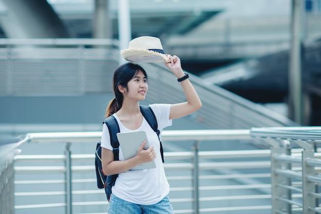 Menina linda estudante sorrindo com laptop e bolsa, conceito de educação