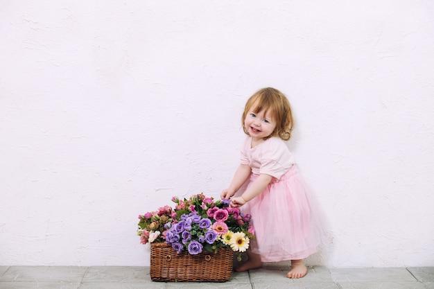 Menina linda, fofa e feliz com flores no fundo da parede branca