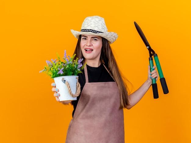 Menina linda jardineira confusa, usando uniforme e chapéu de jardinagem, segurando uma tesoura e segurando uma flor em um vaso de flores para a câmera isolada em um fundo laranja