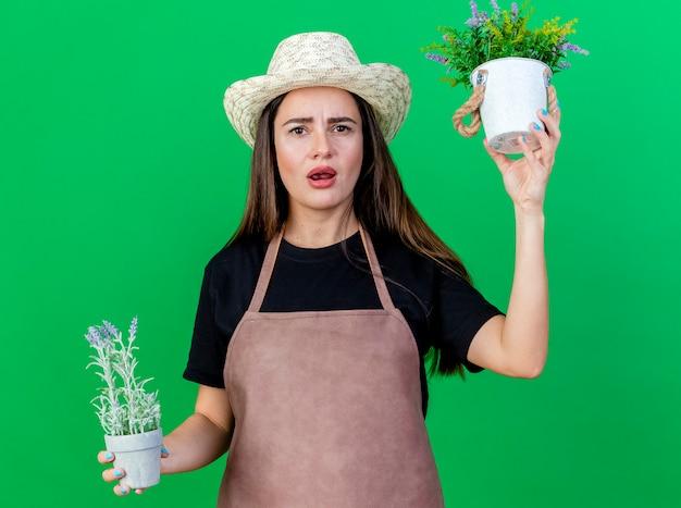 Menina linda jardineira desagradável de uniforme, usando chapéu de jardinagem, segurando flores em um vaso de flores isolado sobre fundo verde