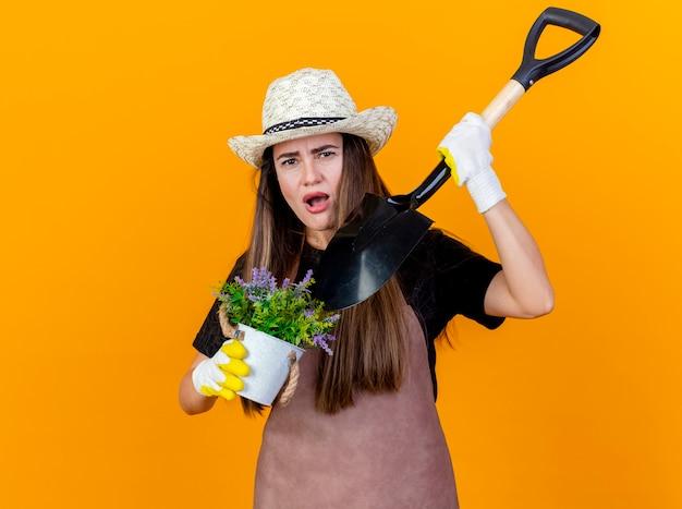 Menina linda jardineira descontente vestindo uniforme e chapéu de jardinagem com luvas segurando e pontas com pá na flor em vaso isolado em fundo laranja