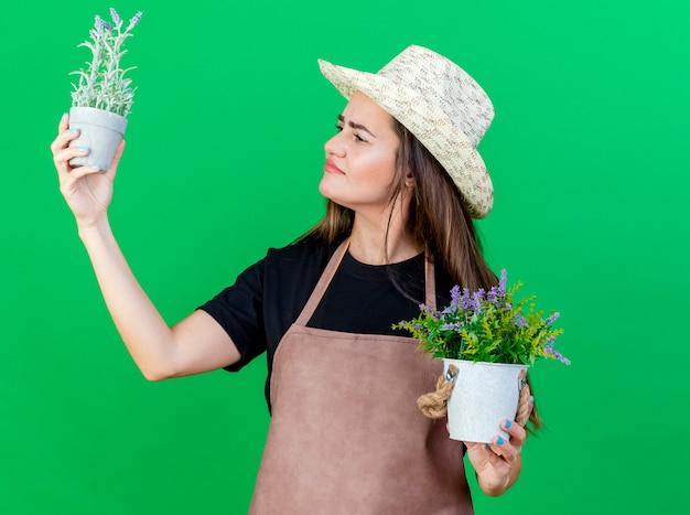 Menina linda jardineira satisfeita de uniforme, usando chapéu de jardinagem, levantando e olhando para uma flor em um vaso de flores isolado no fundo verde