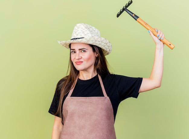 Menina linda jardineira satisfeita de uniforme usando chapéu de jardinagem levantando o ancinho isolado em fundo verde oliva