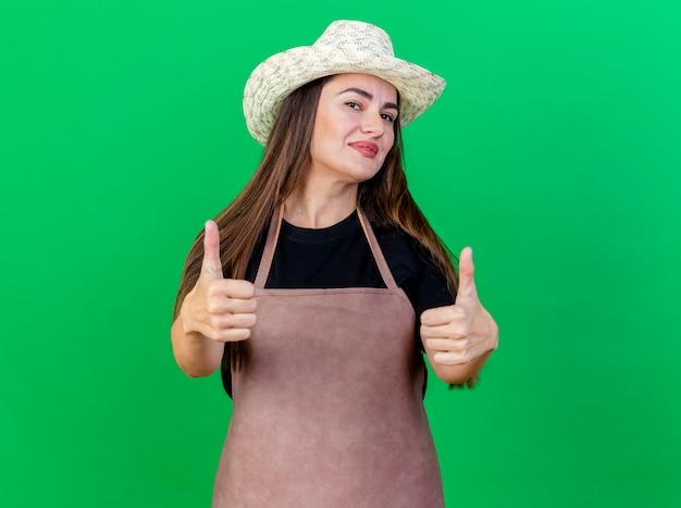 Menina linda jardineira satisfeita de uniforme usando chapéu de jardinagem mostrando os polegares isolados no verde