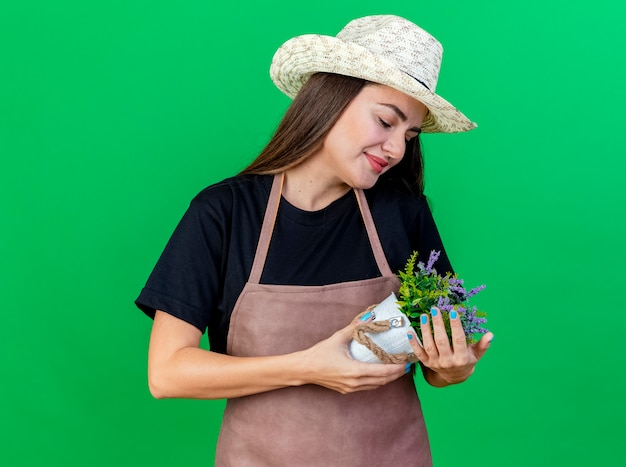 Menina linda jardineira satisfeita de uniforme, usando chapéu de jardinagem, segurando e olhando para uma flor em um vaso de flores isolado no fundo verde