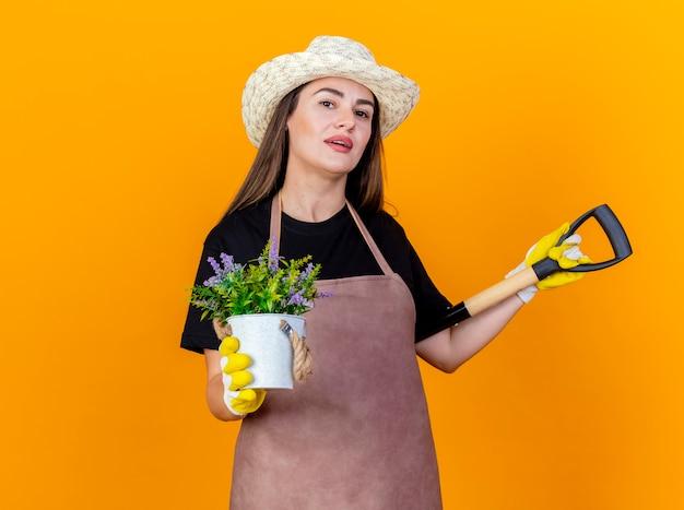 Menina linda jardineira satisfeita vestindo uniforme e chapéu de jardinagem com luvas, colocando a pá no ombro e segurando uma flor em um vaso de flores isolado em um fundo laranja