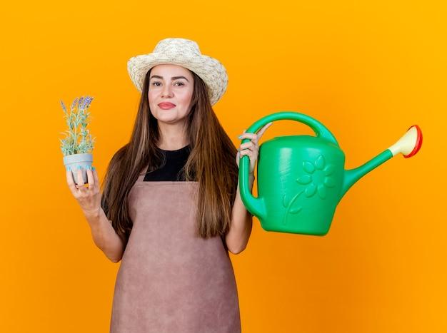 Menina linda jardineira satisfeita vestindo uniforme e chapéu de jardinagem segurando um regador com uma flor em um vaso isolado em um fundo laranja