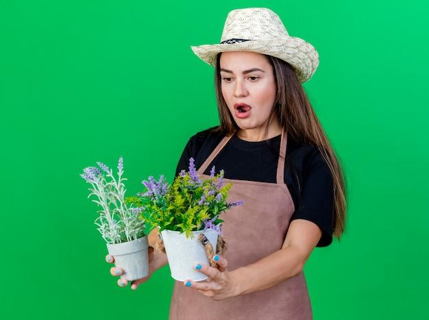 Menina linda jardineira surpresa de uniforme, usando chapéu de jardinagem, segurando e olhando para uma flor em um vaso de flores