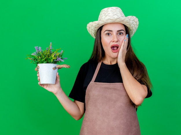 Menina linda jardineira surpresa de uniforme usando chapéu de jardinagem, segurando uma flor em um vaso de flores e colocando a mão na bochecha isolada sobre fundo verde