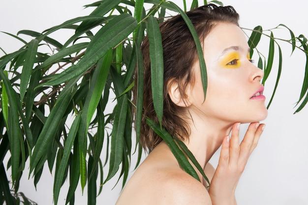 Menina linda jovem adolescente com uma pele perfeita com maquiagem de cor amarela fresca e planta verde. mulher de beleza natural. conceito de tratamento de spa de salão de beleza de cuidados de rosto de cuidados de pele
