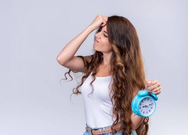 Menina linda jovem estressada segurando o despertador e colocando a mão na cabeça com os olhos fechados na parede branca isolada com espaço de cópia