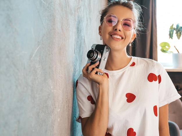 Menina linda jovem fotógrafo tirando fotos usando sua câmera retro