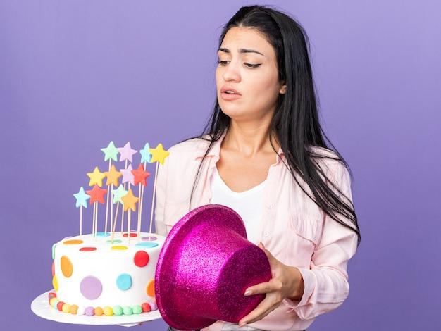 Menina linda jovem insatisfeita segurando um bolo segurando um chapéu e olhando para o bolo na mão