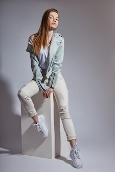 Menina linda jovem modelo em jeans azul branco e camiseta branca, posando no estúdio em fundo branco. beleza natural