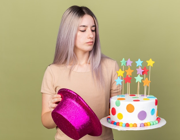 Menina linda jovem segurando um chapéu de festa e olhando para um bolo na mão