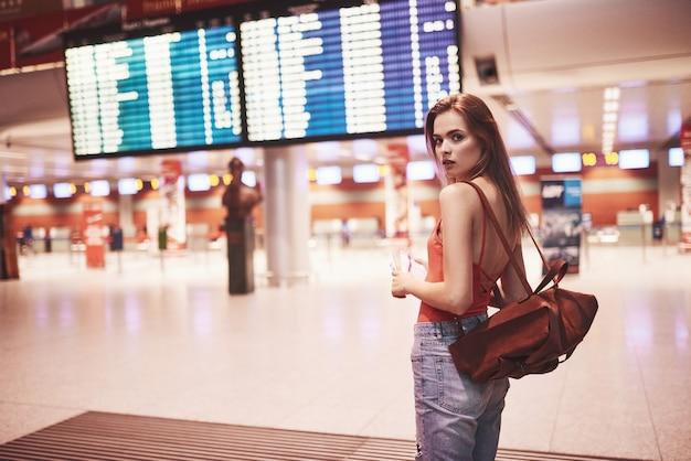Menina linda jovem turista com mochila no aeroporto internacional, perto do quadro de informações de voo.