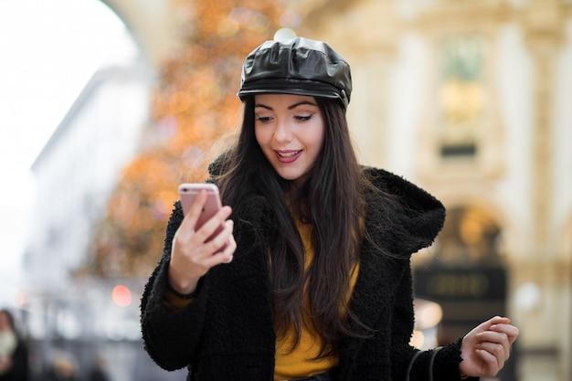 Menina linda jovem turista em milão, fazer compras em milão enquanto estiver usando um smartphone