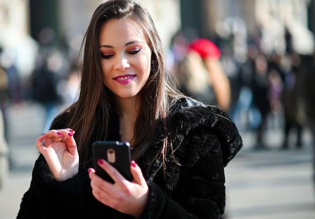 Menina linda jovem turista em milão, usando um smartphone