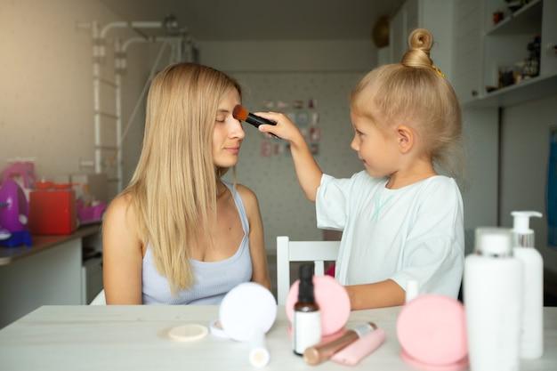 Menina linda maquiadora pinta a mãe em casa