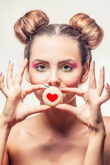 Menina linda modelo com biscoitos doces com corações em uma superfície branca amor dia dos namorados