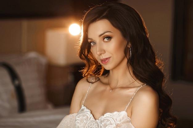 Menina linda modelo com cachos e maquiagem nude. retrato de uma jovem mulher com maquiagem da moda e penteado de casamento. conceito de moda para casamento.