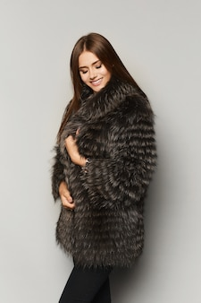 Menina linda modelo com maquiagem perfeita com casaco de pele de luxo, isolada no fundo.