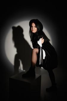 Menina linda modelo com maquiagem suave em um vestido preto curto e um chapéu da moda, olhando para a câmera e posando.