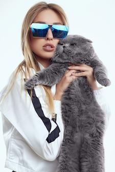 Menina linda modelo com um agasalho posando com um gato gordo de pedigree