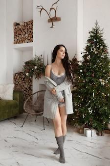 Menina linda modelo em pijamas e meias longas e quentes que passa o dia em casa na véspera de natal