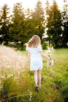 Menina linda modelo em vestido branco correndo no campo, luz solar. mulher feliz livre. tons de cores quentes. foco seletivo.