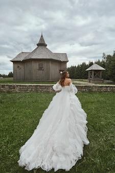 Menina linda modelo em vestido de noiva luxuoso andando no prado em jovem prett do campo.