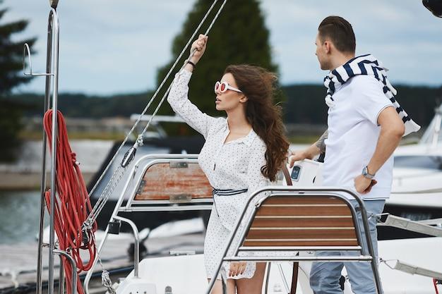 Menina linda modelo morena elegante em vestido elegante curto branco e óculos de sol da moda posando em um iate navio no mar