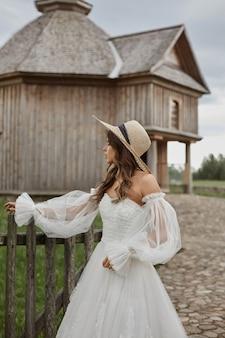 Menina linda modelo no vestido vintage na moda e chapéu de palha para a jovem noiva do campo na moda.