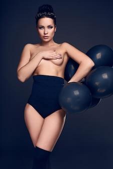 Menina linda modelo nua com balões pretos posando isolado no fundo branco.