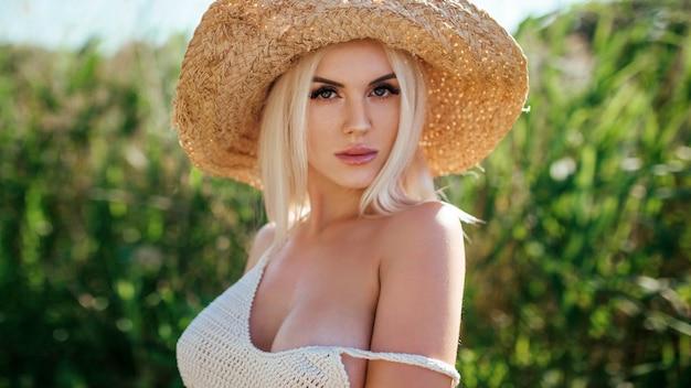 Menina linda modelo posando no campo curtindo a natureza ao ar livre em um chapéu de palha.