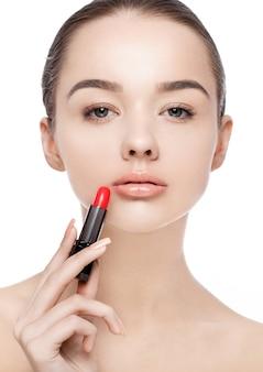 Menina linda modelo segurando a maquiagem do tubo de batom no fundo branco