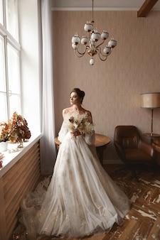 Menina linda modelo usando um vestido de noiva vintage com mangas compridas dentro de casa elegante jovem noiva i ...