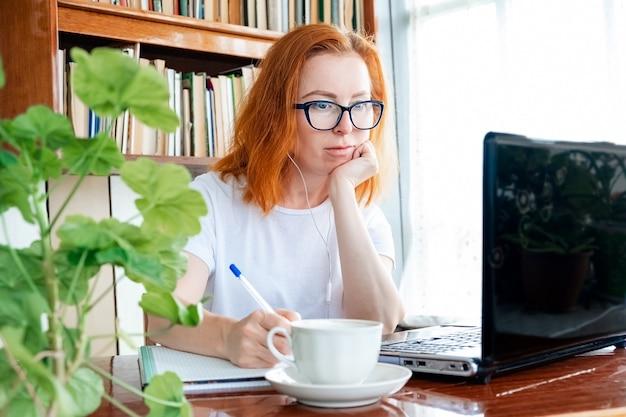 Menina linda mulher com cabelo ruivo e óculos, sentado à mesa em casa e trabalhando no computador. educação a distância online e trabalho remoto.