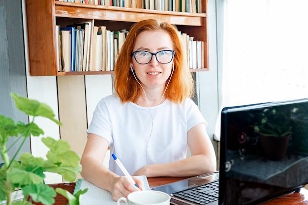 Menina linda mulher com cabelo ruivo e óculos, sentado à mesa em casa e trabalhando no computador, olhando para a câmera e sorrir. educação a distância online e trabalho remoto.
