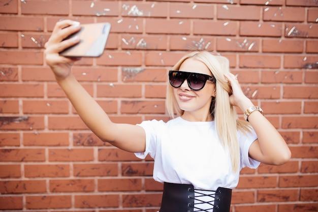Menina linda mulher loira tomando uma selfie no smartphone, posando de pé contra a parede de tijolo vermelho.