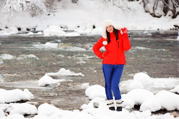 Menina linda na floresta de inverno perto do rio