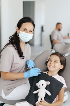 Menina linda no dentista olhando e sorrindo