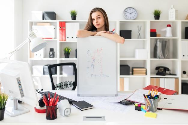 Menina linda no escritório está de pé perto da mesa e colocou as mãos no quadro magnético.