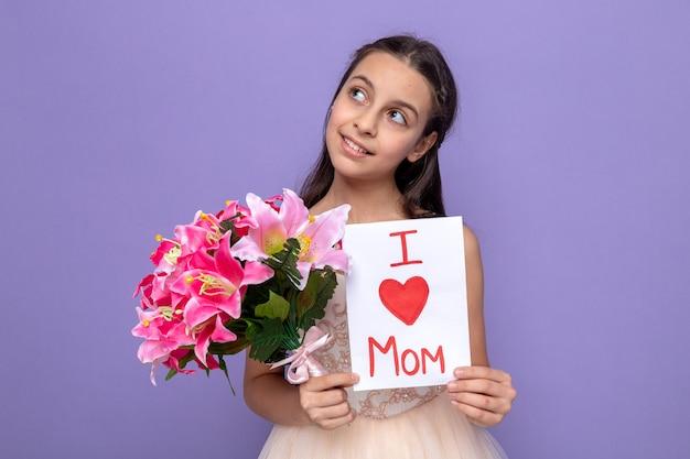 Menina linda no feliz dia das mães segurando o buquê com um cartão de felicitações ao olhar para o lado impressionado