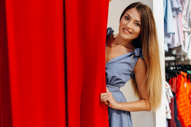Menina linda no vestido azul, experimentando roupas no provador