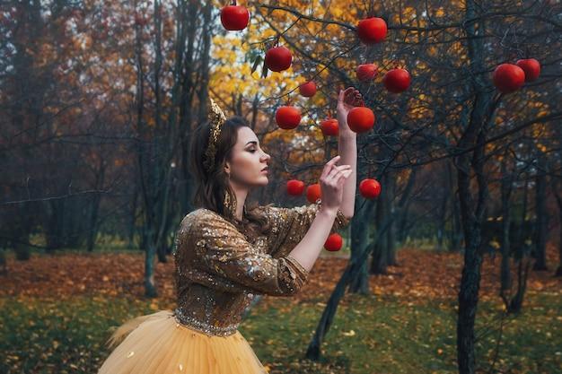 Menina linda no vestido de ouro na floresta de outono