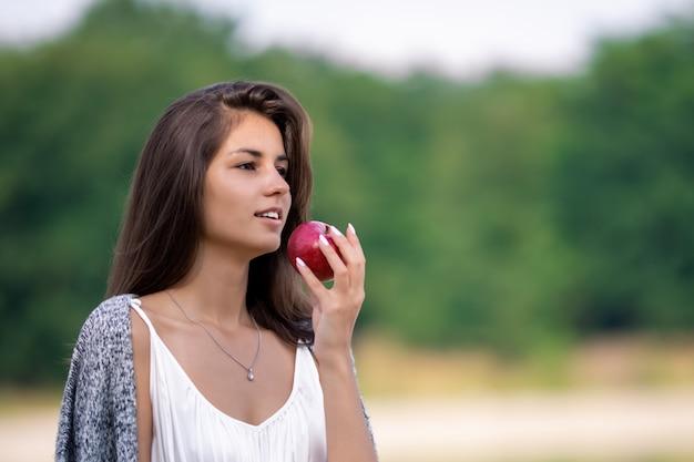 Menina linda num vestido branco, comendo maçã orgânica madura.