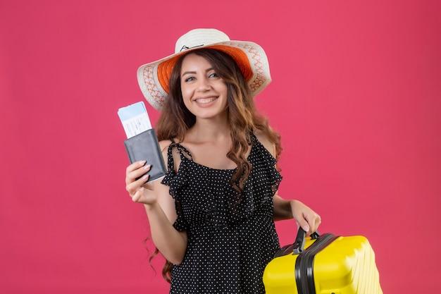 Menina linda num vestido de bolinhas com chapéu de verão em pé com uma mala segurando as passagens aéreas, olhando para a câmera sorrindo alegremente sobre o fundo rosa