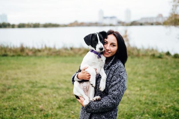 Menina linda passeando com o cachorro. fêmea bonito que joga com os filhotes de cachorro ao ar livre na natureza. proprietário com adoráveis pequenos caninos jovens com olhos de pena.