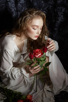 Menina linda primavera está sentada no chão com flores rosas nas mãos dela. a mulher em um vestido branco está sonhando, uma imagem romântica. loira com cabelos cacheados